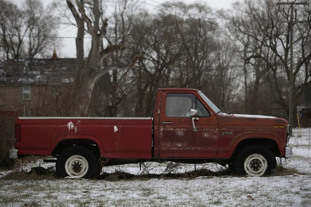 An older Ford F-250 pick-up truck with rust spots sits in the yard of a home in Detroit, Michigan January 8, 2015. (Photo by Joshua Lott/Reuters)