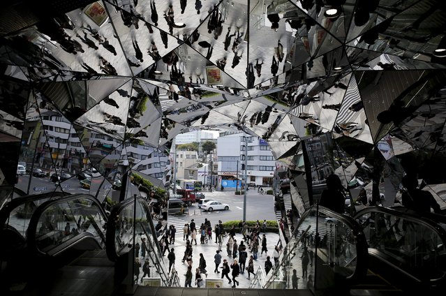 People are reflected in mirrors at an entrance to a department store in Tokyo, Japan, in this November 11, 2015 file photo. Japan is expected to report restail sales adat this week. (Photo by Toru Hanai/Reuters)