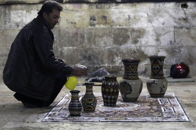 Mohamad Al-Bayoush, a supervisor inside a mosaic workshop, sprays mosaic pots with water in Kafranbel town in the Idlib governorate January 17, 2015. (Photo by Khalil Ashawi/Reuters)