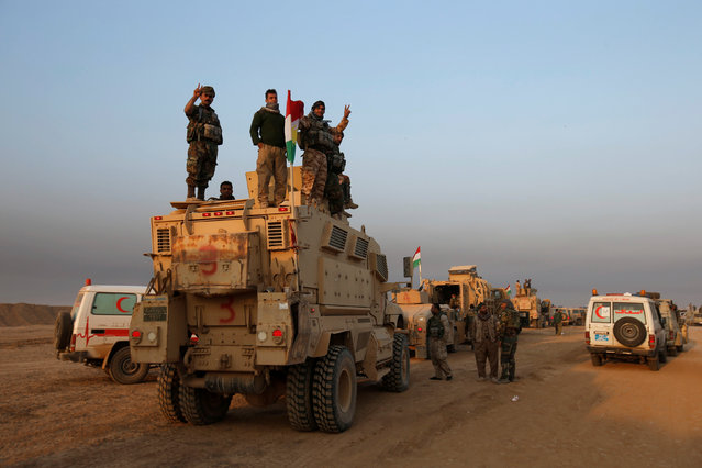 Peshmerga forces stand on a military vehicle in the town of Bashiqa, east of Mosul, during an operation to attack Islamic State militants in Mosul, Iraq, November 7, 2016. (Photo by Azad Lashkari/Reuters)