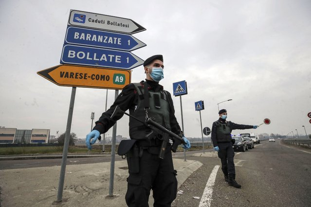"Carabinieri officers patrol one of the main access road to Bollate, in the outskirts of Milan, Italy, Thursday, February 18, 2021. Four cities in Lombardy region, including one in the province of Brescia, have been placed under the strictest ""red zone"" lockdown measures following spikes of infections traced to the highly contagious British variant. Other red zones have been imposed in cities in the central Italian regions of Umbria, Tuscany, Abruzzo and Lazio, sparking calls for another nationwide lockdown from hospital doctors who are once again seeing their ICU beds fill up. (Photo by Luca Bruno/AP Photo)"