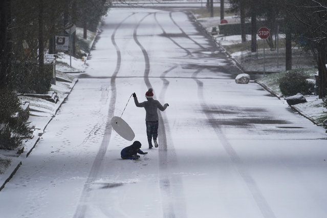 Children play with a sled as snow begins to accumulate, Thursday, February 18, 2021, in San Antonio. Snow, ice and sub-freezing weather continue to wreak havoc on the state's power grid and utilities. (Photo by Eric Gay/AP Photo)