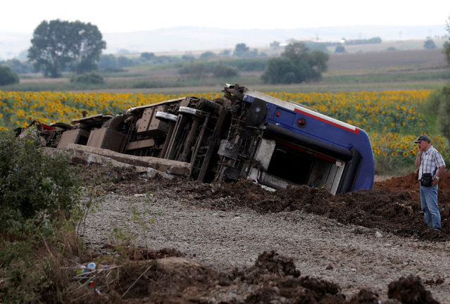 A man talks on his mobile phone at the scene where a passenger train derailed on Sunday, near Corlu in Tekirdag province, Turkey July 9, 2018. (Photo by Osman Orsal/Reuters)