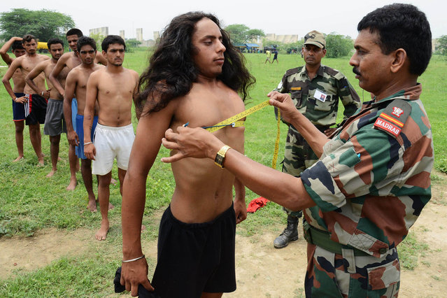 An Indian officers measures a candidate during a physical fitness test at an Indian Army recruitment rally at Khasa, some 15 Kms from Amritsar, on July 15, 2013.  The Indian Army is a voluntary service and the world's largest standing volunteer army, with over a million active personnel and just under a million in reserve. (Photo by Narinder Nanu/AFP Photo)