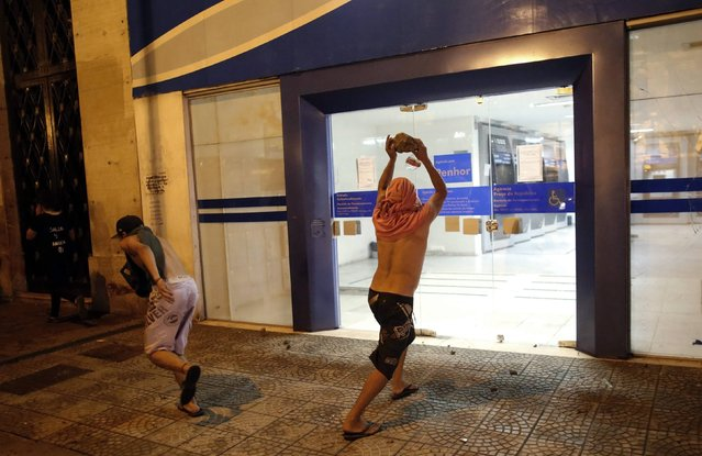 A demonstrator attacks a Caixa bank branch during a protest against fare hikes for city buses, subway and trains in Sao Paulo January 23, 2015. (Photo by Nacho Doce/Reuters)