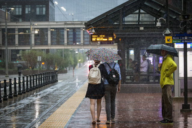 Commuters walk to the Government Center Light Rail station during the rain in downtown Minneapolis, Thursday, July 12, 2018. Powerful overnight storms dumped significant amounts of rain in northeast and east-central Minnesota, leading to floods and washed-out roads in some areas. (Photo by Leila Navidi/Star Tribune via AP Photo)