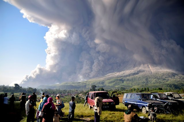 People watch as Mount Sinabung erupts in Karo, North Sumatra, Indonesia, Tuesday, March 2, 2021. The 2,600-meter (8,530-feet) volcano spewed materials a few thousand meters (yards) into the sky and deposited ash on nearby villages. (Photo by AP Photo/Stringer)