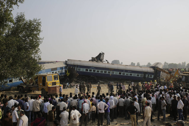 People gather after 14 coaches of an overnight passenger train rolled off the track near Pukhrayan village Kanpur Dehat district, Uttar Pradesh state, India, Sunday, November 20, 2016. Dozens were killed and dozens more were injured in the accident. (Photo by Rajesh Kumar Singh/AP Photo)