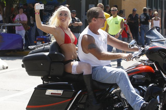 A biker and his passenger make their way down Main Street in Sturgis during the motorcycle rally, on August 7, 2013 afternoon as she takes video with her phone along the way. (Photo by Chris Huber)