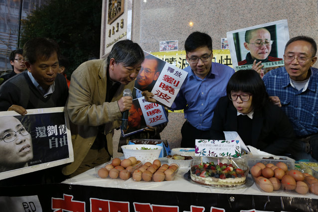 Pro-democracy demonstrators blow a candle of a birthday cake to celebrating 60th birthday of jailed Nobel Peace Prize laureate Liu Xiaobo in Hong Kong, China December 28, 2015. Hong Kong protesters demanded the release of Liu, who was sentenced to imprisonment six years ago on Christmas day. (Photo by Tyrone Siu/Reuters)