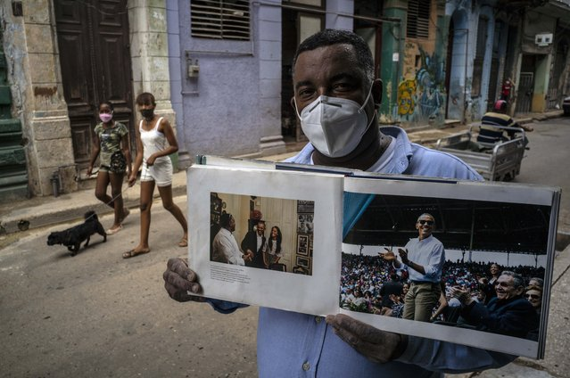 "In this October 22, 2020 file photo wearing a face mask amid the new coronavirus pandemic, Cristobal Marquez, owner of ""Cristobal's"", the restaurant where Michelle and Barak Obama had lunch during their visit to Cuba in 2016, shows the book made by White House photographer Pete Souza, in Havana, Cuba. While Joe Biden was part of an administration that reestablished diplomatic ties with Cuba, loosened travel restrictions and made it easier for Cubans in the United States to send money home, President Donald Trump has increased sanctions on companies that do business with the island's government and even banned Americans from staying in Cuban state-owned hotels. (Photo by Ramon Espinosa/AP Photo/File)"