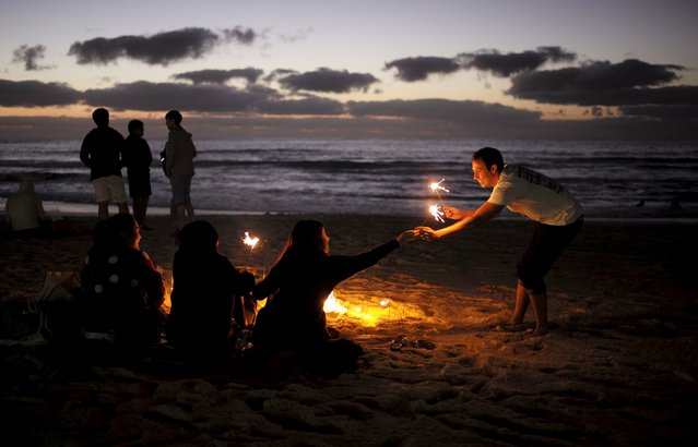 A new year reveller (R) receives a gift of sparklers as hundreds of partygoers await the first sunrise of the new year on Australia's Bondi Beach in Sydney, January 1, 2016. (Photo by Jason Reed/Reuters)