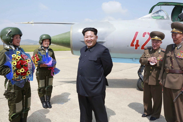 North Korean leader Kim Jong Un smiles as he attends a flight training session by female fighter pilots Jo Kum Hyang and Rim Sol in this undated photo released by North Korea's Korean Central News Agency (KCNA) on June 22, 2015. (Photo by Reuters/KCNA)