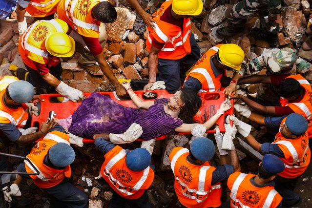 Rescue workers carry a victim across the rubble after the collapse of two residential buildings in Vadodra city, located in the western Indian state of Gujarat, on August 28, 2013. At least seven people died. (Photo by Amit Dave/Reuters)