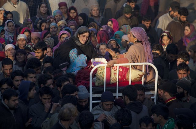 The mother  and sister of  Farooq Ahmed Bhat wail during his funeral procession in Palhalan, some 35 kilometers (22 miles) north of Srinagar, Indian controlled Kashmir, Tuesday, February 10, 2015. Hundreds of angry protesters clashed with Indian authorities on Tuesday at the funeral of the young man killed during a demonstration in disputed Kashmir. Separatists called for a daylong strike in the tense Himalayan territory. (Photo by Dar Yasin/AP Photo)