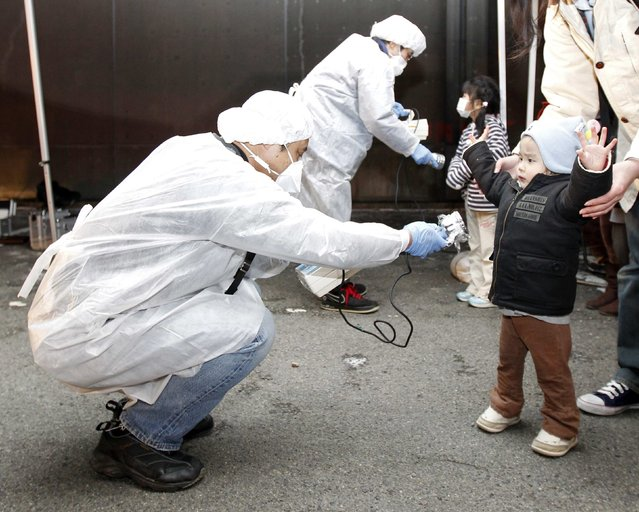 Officials in protective gear check for signs of radiation on children who are from the evacuation area near the Fukushima Daini nuclear plant in Koriyama in this March 13, 2011 file photo. The biggest earthquake to hit Japan on record struck the northeast coast, triggering a 10-metre tsunami that swept away everything in its path, including houses, ships, cars and farm buildings on fire and caused the meltdown of the Fukushima nuclear power plant. (Photo by Kim Kyung-Hoon/Reuters)