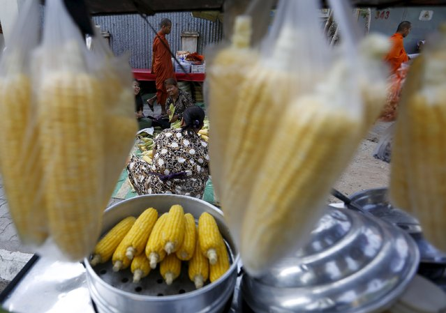 Buddhist monks walk pass as vendors clean corn cobs before steaming them to be sold in a street in central Phnom Penh December 30, 2015. (Photo by Samrang Pring/Reuters)