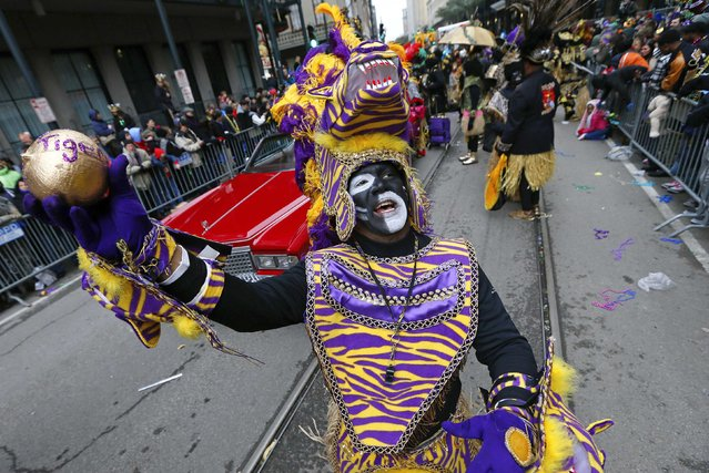 A member of the Zulu Social Aid and Pleasure Club throws a coconut on Mardi Gras in New Orleans, Louisiana February 17, 2015. (Photo by Jonathan Bachman/Reuters)
