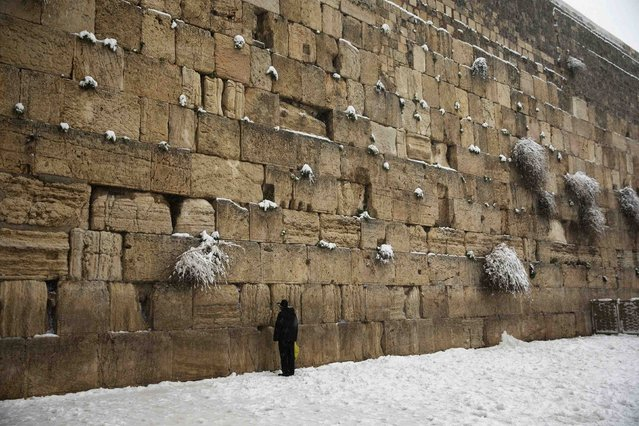 A man prays in the snow at the Western Wall, Judaism's holiest prayer site, in Jerusalem's Old City February 20, 2015. (Photo by Ronen Zvulun/Reuters)