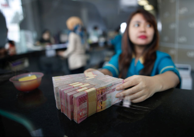 A teller at a money changer handles Indonesia rupiah bank notes in Jakarta, Indonesia November 11, 2016. (Photo by Darren Whiteside/Reuters)