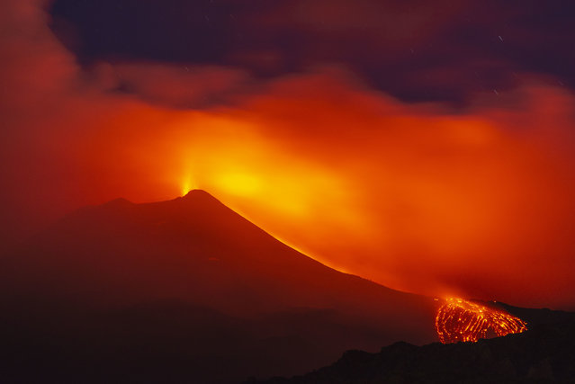 """Mount Etna volcano spews lava during an eruption early Saturday, August 25, 2018. Mount Etna in Sicily has roared back into spectacular volcanic action, sending up plumes of ash and spewing lava. Italy's National Institute of Geophysics and Vulcanology (INGV) says that the volcano, which initially """"re-awoke"""" in late July, sprang into fuller action Thursday evening by shooting up chunks of flaming lava as high as 150 meters (500 feet) almost constantly. (Photo by Salvatore Allegra/AP Photo)"""