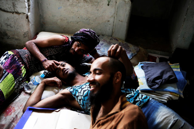 Rodrigo (R), 26, Wam (C), 24, and Teflon, 19, members of the lesbian, gay, bisexual and transgender (LGBT) community who have been invited to live in a building that the roofless movement has occupied, relax in downtown Sao Paulo, Brazil, November 8, 2016. (Photo by Nacho Doce/Reuters)