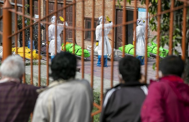 Family members watch as Nepalese army personnel in PPE suits salute to pay tribute to the COVID-19 victims before cremating their bodies near Pashupatinath temple in Kathmandu, Nepal, Friday, May 7, 2021. (Photo by Niranjan Shrestha/AP Photo)