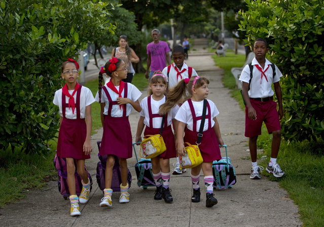 In this September 23, 2013 photo, from left to right, nine-year-old twins Camila and Carla Rodriguez, six-year-old twins Asley and Aslen Velazquez, and 11-year-old twin brothers Arian and Adrian Cueto walk together to school in Havana, Cuba. The twins are three sets of 12 living along two consecutive blocks in western Havana, ranging in age from newborns to senior citizens. (Photo by Ramon Espinosa/AP Photo)