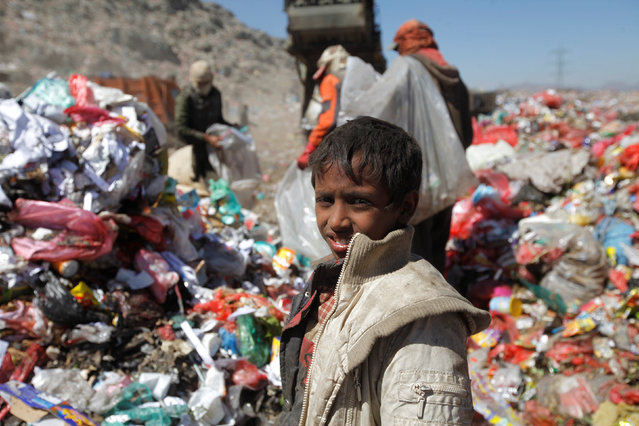A boy looks as he stands on a pile rubbish to collect recyclable items at a landfill on the outskirts of Sanaa, Yemen November 16, 2016. (Photo by Mohamed al-Sayaghi/Reuters)