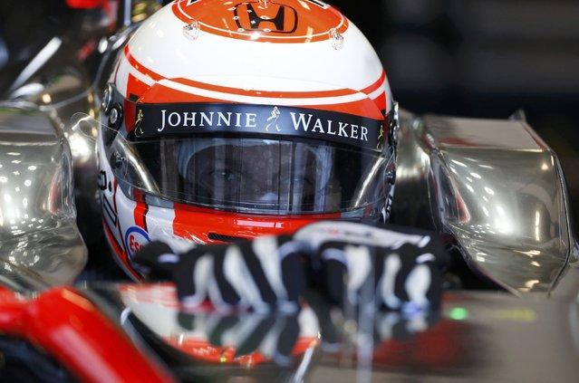 McLaren Formula One driver Jenson Button of Britain sits in his car in his garage during the first practice session of the Australian F1 Grand Prix at the Albert Park circuit in Melbourne March 13, 2015.  REUTERS/Brandon Malone