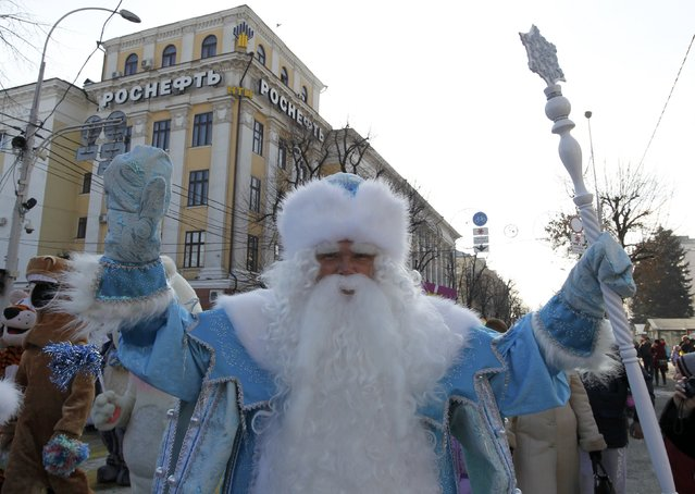 A man dressed as Father Frost, Russian equivalent of Santa Claus, walks past the office of Russian oil company Rosneft during a festive procession as part of the upcoming New Year and Christmas celebrations in Krasnodar, southern Russia, December 17, 2016. (Photo by Eduard Korniyenko/Reuters)
