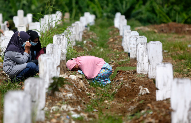 A woman cries before her husband's grave at a cemetery for victims of COVID-19 in Jakarta, Indonesia, 17 May 2021. The Jakarta government allowed residents toresume visits to the city's Public Cemetery on 17 May amid the ongoing coronavirus pandemic. (Photo by Adi Weda/EPA/EFE)