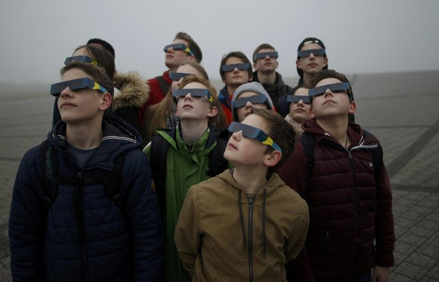 """Pupils pose with their safety glasses as they try to view a partial solar eclipse through thick fog at """"Halde Hoheward"""" in the western city of Herten March 20, 2015. A partial eclipse was visible on Friday, the first day of northern spring, across parts of Africa, Europe and Asia. The total eclipse of the sun was only be visable in the Faroe Islands and the Norwegian archipelago of Svalbard in the Arctic Ocean. (Photo by Ina Fassbender/Reuters)"""