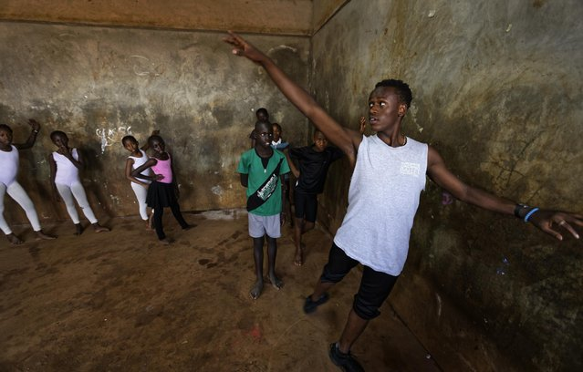 In this photo taken Friday, December 9, 2016, young ballerinas receive instruction from Kenyan ballet dancer Joel Kioko, 16, right, in a room at a school in the Kibera slum of Nairobi, Kenya. (Photo by Ben Curtis/AP Photo)