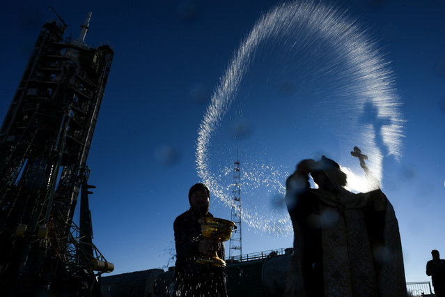 A Russian Orthodox priest blesses the Soyuz MS-11 spacecraft at the launch pad of the Russian-leased Baikonur cosmodrome on December 2, 2018. The launch of the Soyuz MS-11 spacecraft with members of the International Space Station (ISS) expedition 58/59, Russian cosmonaut Oleg Kononenko, NASA astronaut Anne McClain and David Saint-Jacques of the Canadian Space Agency is scheduled on December 3, 2018 from the Russian-leased Kazakh Baikonur cosmodrome. (Photo by Kirill Kudryavtsev/AFP Photo)