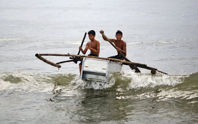 Boys maneuver their boat, made from a broken fridge and bamboo, to the beach in Tanauan November 20, 2013. (Photo by Damir Sagolj/Reuters)