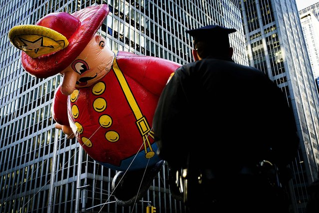 A police officer stands on Sixth Avenue as a giant fireman balloon passes. (Photo by John Minchillo/Associated Press)