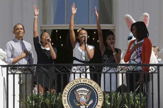 U.S. President Barack Obama (L) and first lady Michelle Obama (R) stand with their hands over their hearts as singers ID4GIRLS perform the national anthem to kick off the annual Easter Egg Roll at the White House in Washington April 6, 2015. (Photo by Jonathan Ernst/Reuters)