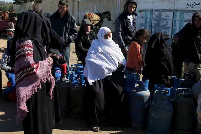 Palestinians wait to fill cooking gas canisters outside a gas filling station in Rafah in the southern Gaza Strip January 28, 2016. The strip, home for 1.95 million people, has been experiencing a shortage of cooking gas, local residents said. REUTERS/Ibraheem Abu Mustafa