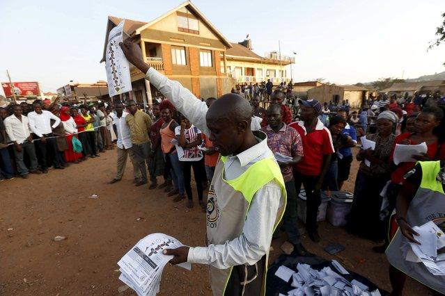 Electoral officials count votes at a polling station in Uganda's capital Kampala February 18, 2016 as voting closes. (Photo by James Akena/Reuters)