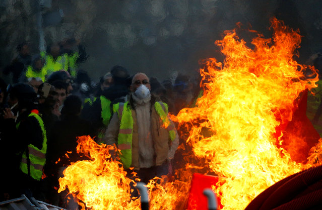 "Protesters wearing yellow vests are seen behind a fire as they attend a demonstration of the ""yellow vests"" movement in Angers, France, January 19, 2019. (Photo by Stephane Mahe/Reuters)"