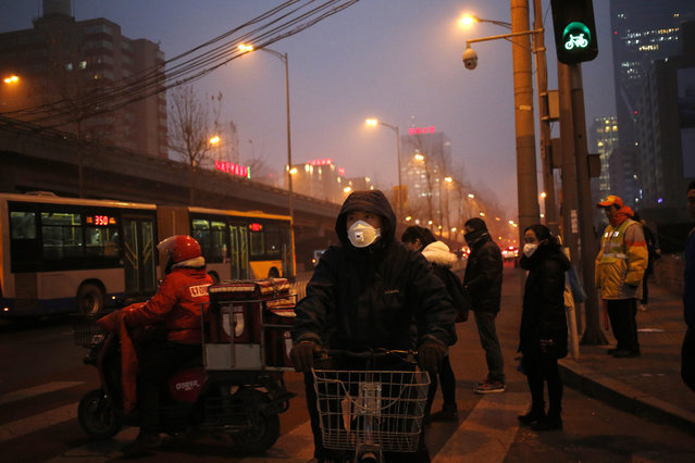 Bicycle riders wearing masks wait during heavy traffic on a smoggy day in Beijing, China, 04 January 2017. China issued its first-ever national red alert for severe fog on 04 Jan 2017, after 24 of its cities across the country have already issued red alerts for air pollution problems. Red is the highest level in the country's four-tier warning system. (Photo by How Hwee Young/EPA)