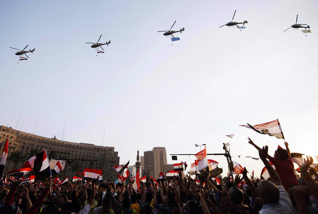 Egyptian people wave the national flag as army helicopters fly above Egypt's landmark Tahrir square on July 4, 2013. (Photo by Gianluigi Guercia/AFP Photo)
