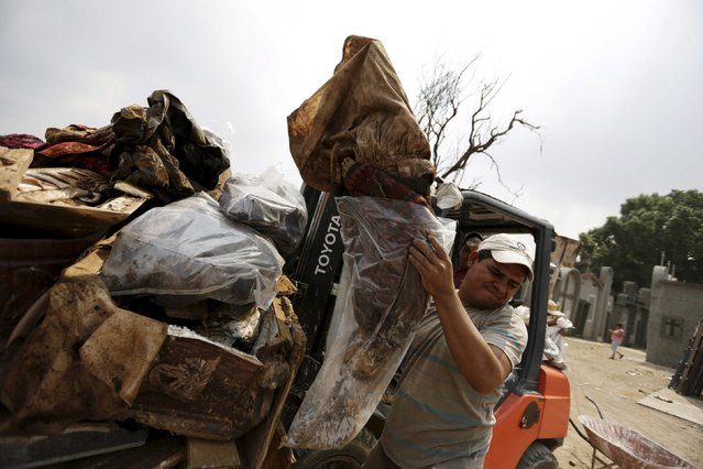 A grave cleaner holds a mummified body in a plastic bag near a forklift with discarded coffins and corpses in a plastic bags during exhumation works at General Cemetery in Guatemala City, April 15, 2015. (Photo by Jorge Dan Lopez/Reuters)