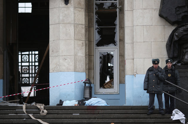 Russian policemen stand guard next to a body at the explosion site on the entrance of the Volgograd railway station in Volgograd, Russia, 29 December 2013. (Photo by EPA/STR)