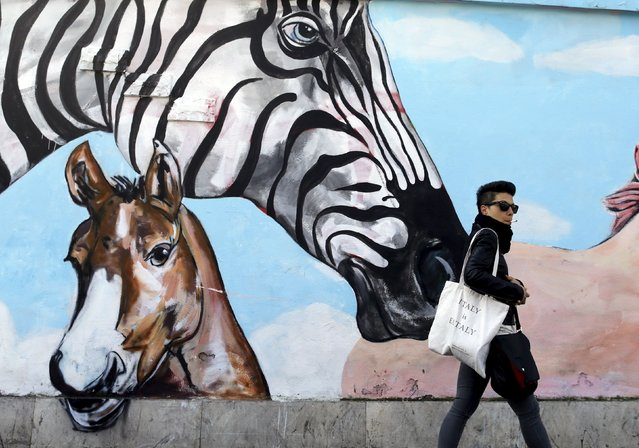 A woman walks past a mural in downtown Rome, April 15, 2015. (Photo by Tony Gentile/Reuters)
