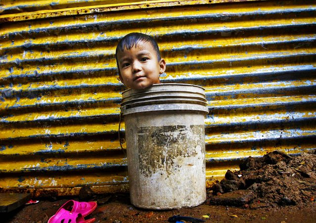 A boy sits in a bucket as he plays while waiting for his mother to fetch water from a nearby hand pump to bathe him in the southern Indian city of Chennai, December 30, 2013. (Photo by Reuters/Babu)