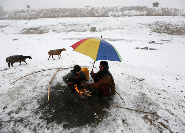 Afghan men warm themselves by a fire on a snowy day in Kabul, Afghanistan January 14, 2017. (Photo by Mohammad Ismail/Reuters)