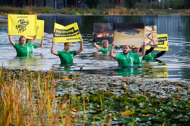 Greenpeace activists protest in a lake ahead of the Munich Motor Show IAA Mobility 2021 in Munich, Germany, September 7, 2021. (Photo by Wolfgang Rattay/Reuters)
