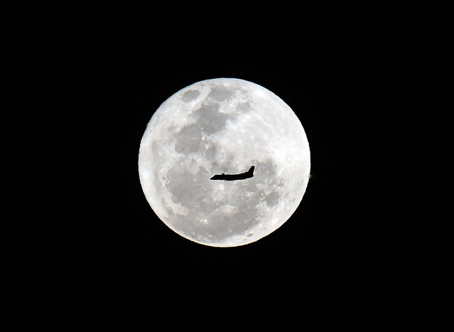 A plane flies in front of a full moon in Sydney on September 25, 2018. (Photo by Saeed Khan/AFP Photo)